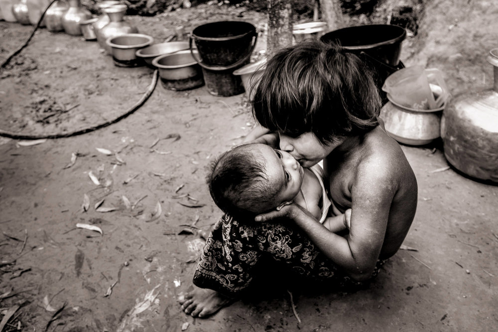 Rohingya refugee Umairhair Hasumiya, 7, plays with her 3-month-old brother Rihas as they wait for water in the Musoni Noyapara refugee camp in Bangladesh on Oct. 9, 2017. A crisis of water-borne disease and diarrhea has gripped the camp where potable water is not available. A Bangladeshi neighbor offers water from her tap twice a day, but many of the camp's residents lay listless and ill from the unsanitary and unhygienic conditions. Fears of an epidemic are growing as cholera is endemic in Bangladesh.
