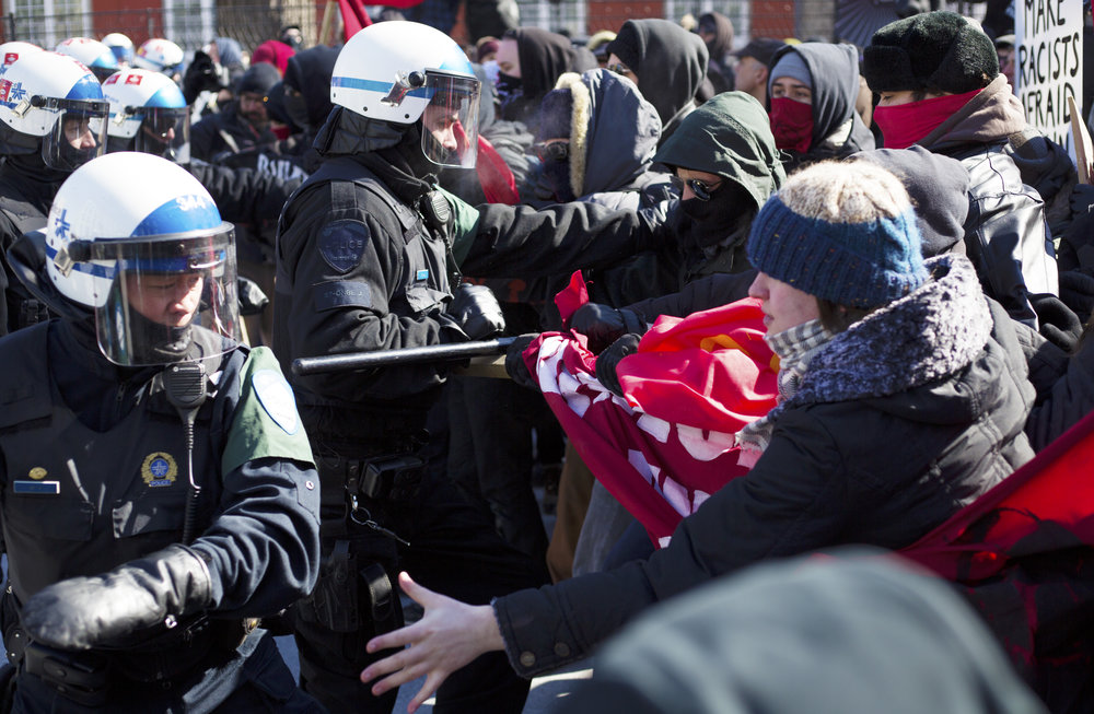 Montreal riot police swings a baton at a protestor at a demonstration against fascism (March 4 2017)
