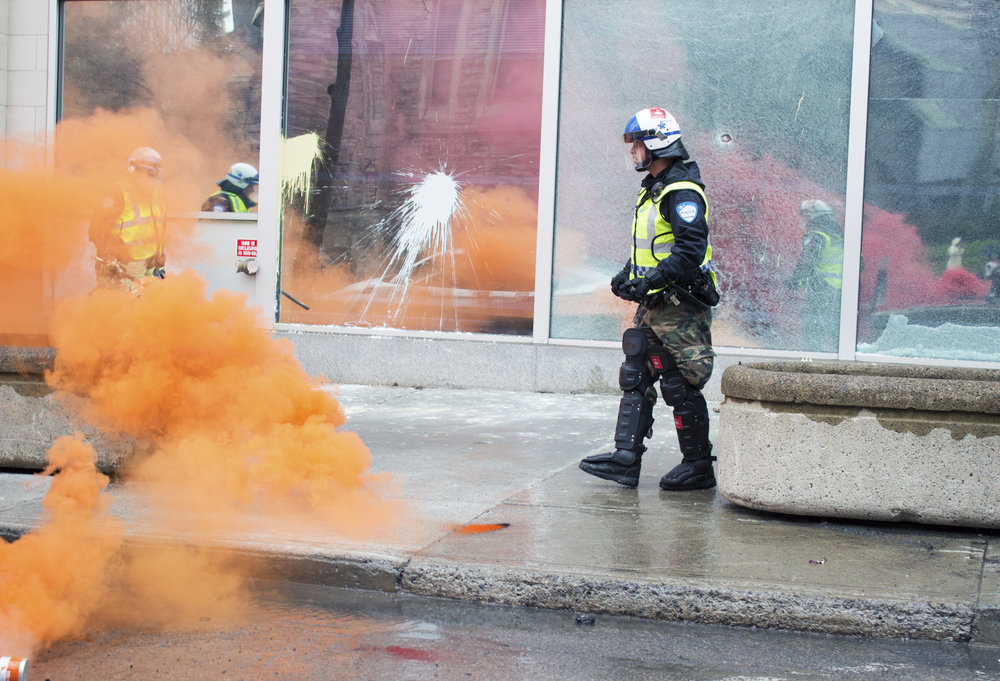 Police walks past a damaged police station during an anticapitalist May Day demonstration in Montreal (May 1 2016)