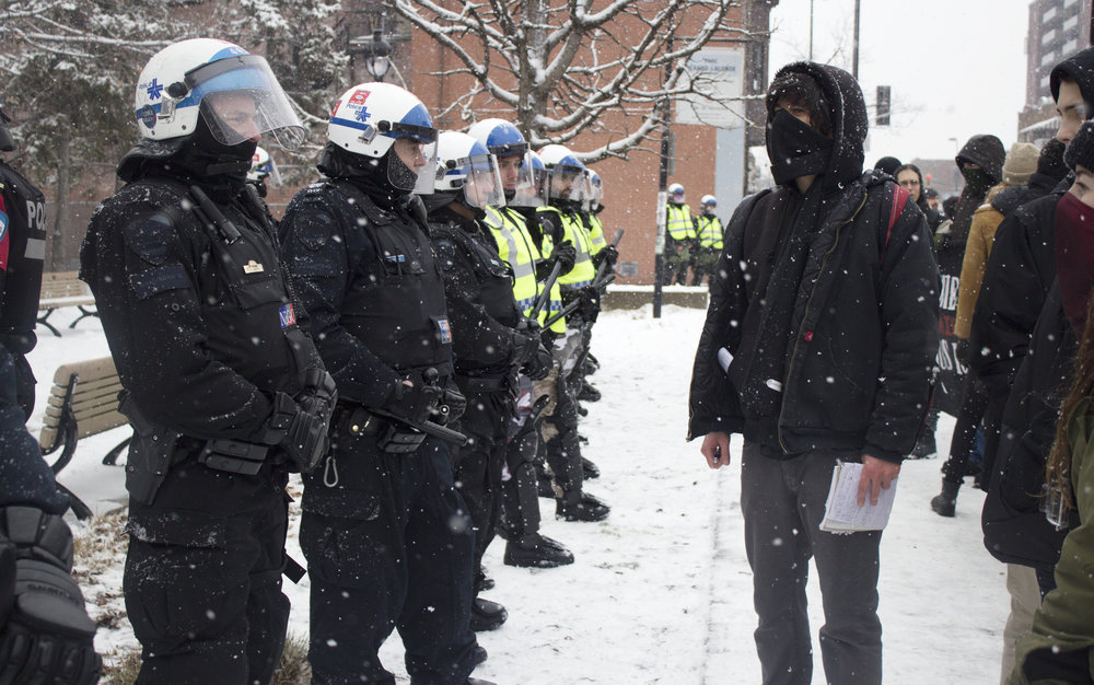 Protestor confronts a line of SPVM riot police during an anti fascist protest against PEGIDA in Montreal (February 6 2016)