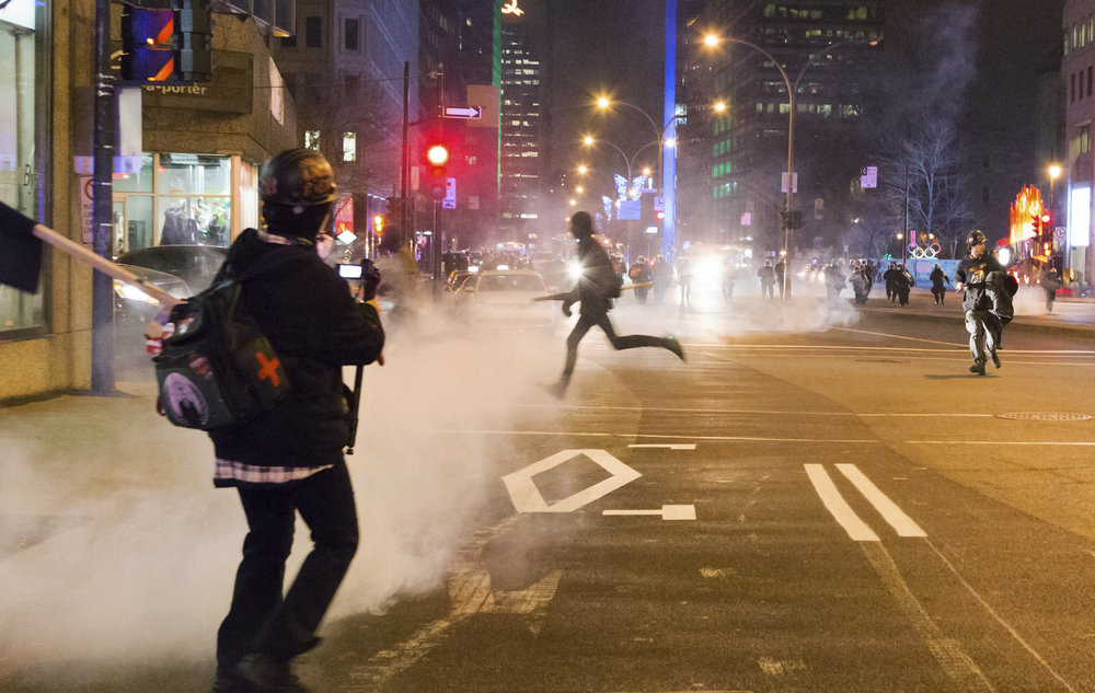 Black Bloc protester runs from tear gas and riot police at an anticapitalist night demonstration in downtown Montreal (December 13 2015)