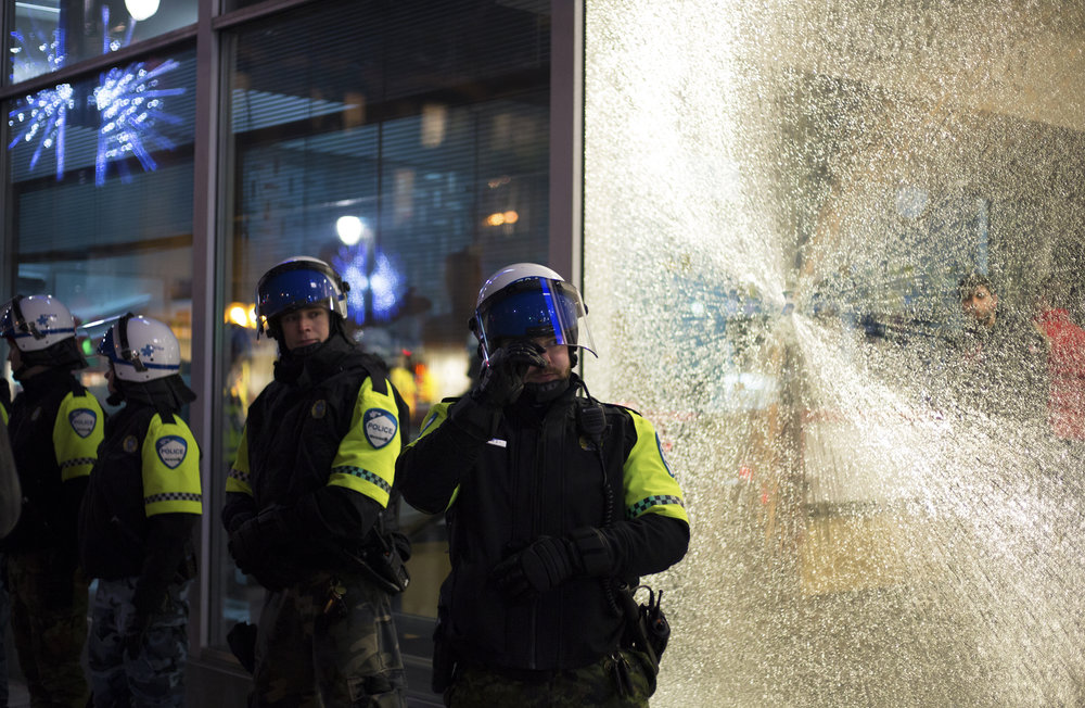 SPVM officers guard a police station after attacked by demonstrators during a protest against Donald Trump in downtown Montreal (January 21 2017)