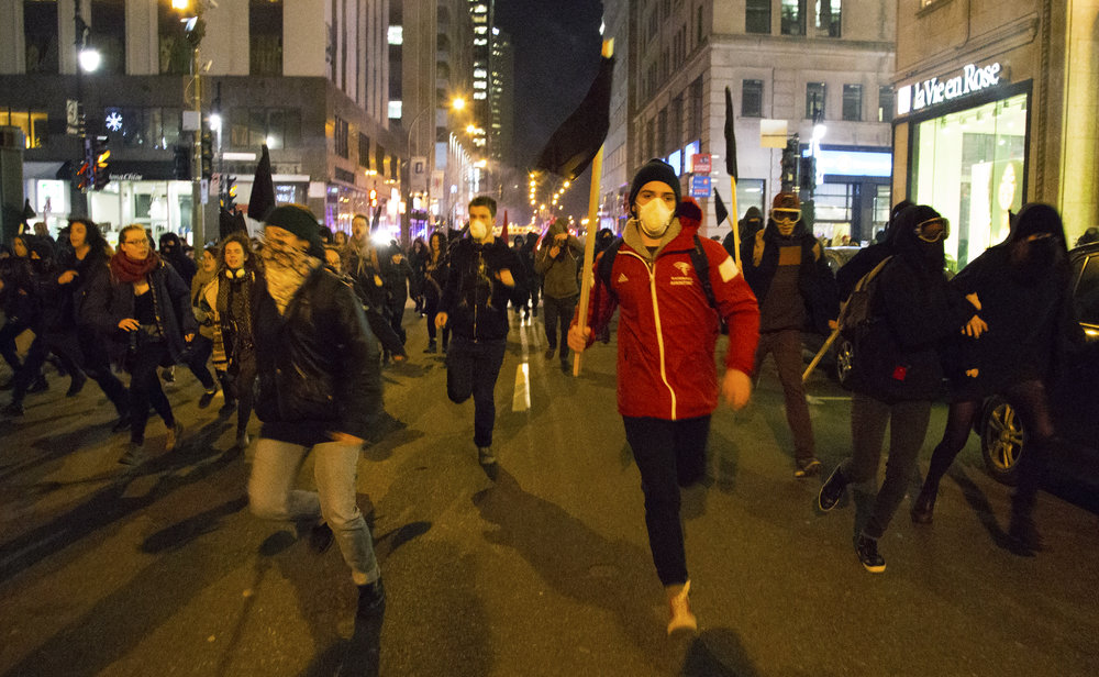 Protesters run from Montreal riot police and tear gas during a December 3 2016 anticapitalist night demonstration.    Full story: https://thelinknewspaper.ca/article/anti-austerity-demonstrators-chased-by-police-through-downtown-montreal