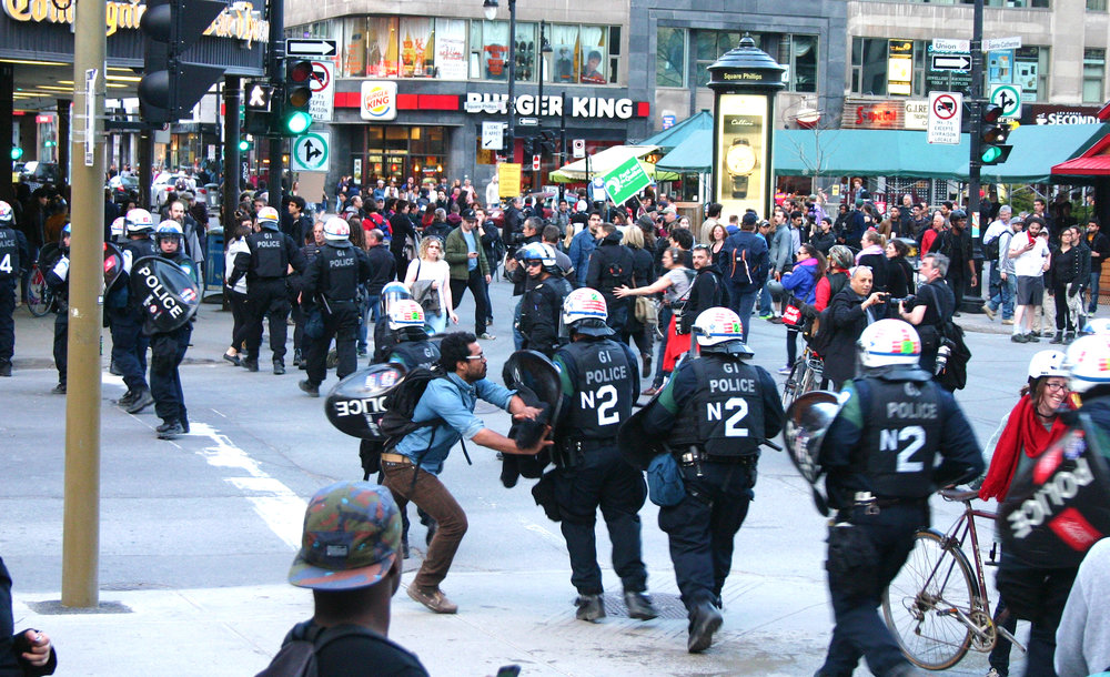 A protester challenges a charging riot police line at a May Day demonstration in Montreal (May 1 2015)