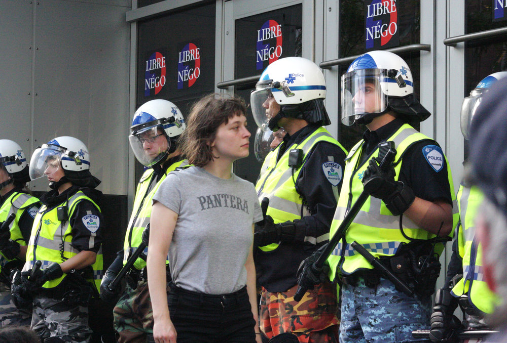 Woman stares down riot police at a silent demonstration against police brutality in Montreal (June  9 2015)