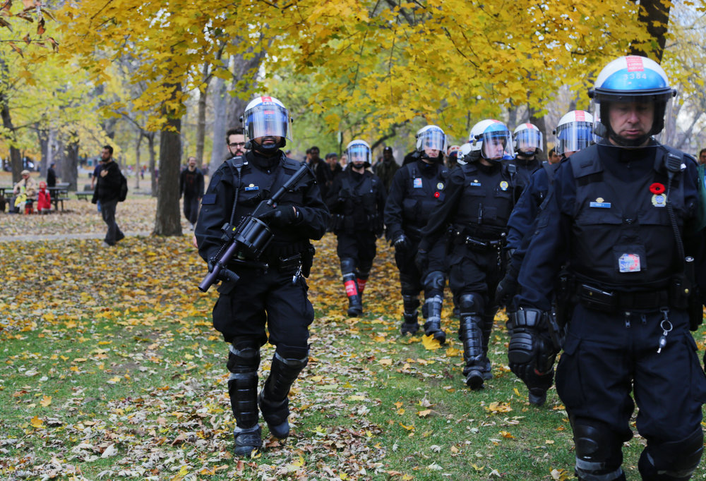 Montreal riot police walk through a park in autumn during a demonstration for increased public funding. (November 5 2015)