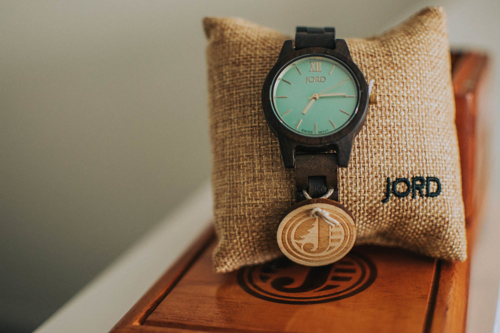 brown sandalwood jord watch with mint face in front of the box and resting on the ledge of a stairway