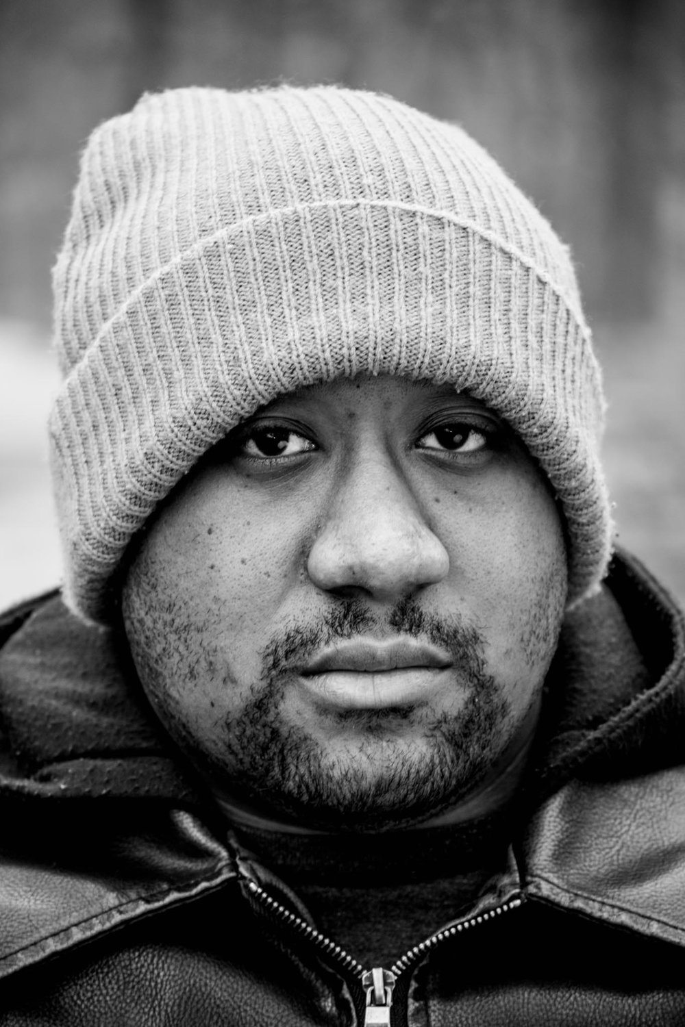 black and white photo of black man in colder outdoor setting wearing a knitted bean cap