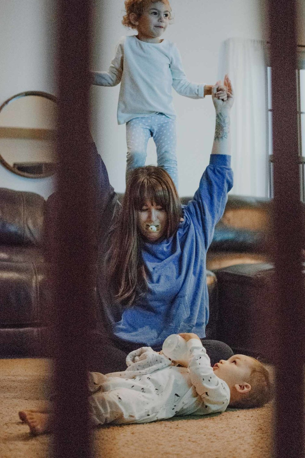 mother looking at a male child holding his bottle while lying on the floor and daughter standing on the shoulders of the mother while using the mother's hands to balance in a living room, taken through a baby gate