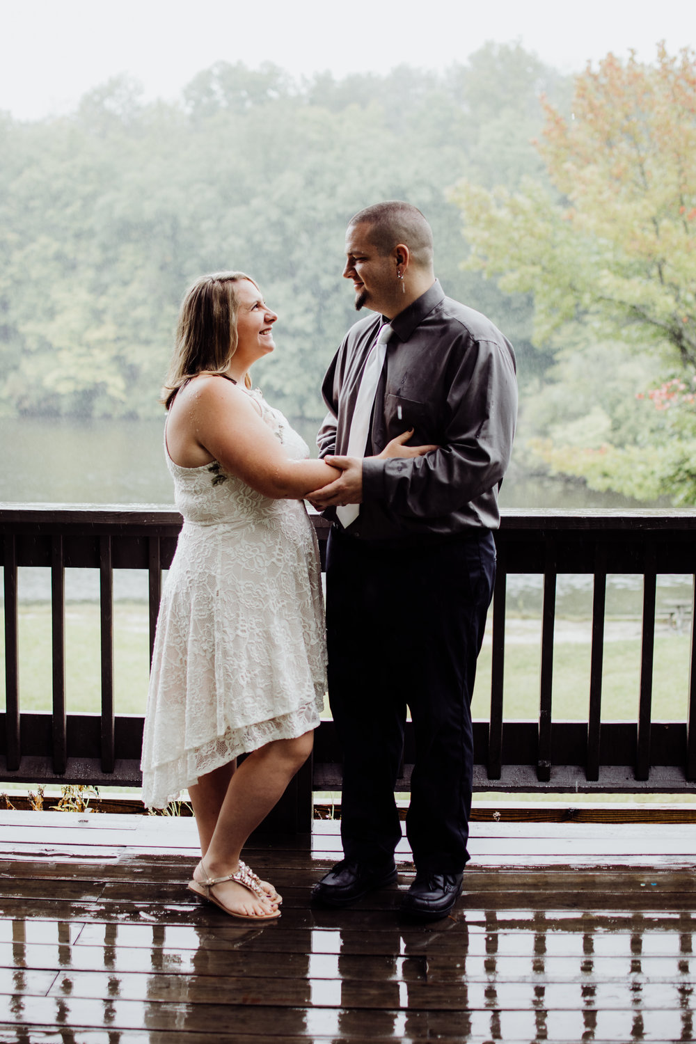 couple on the deck in the rain after getting married by a lake