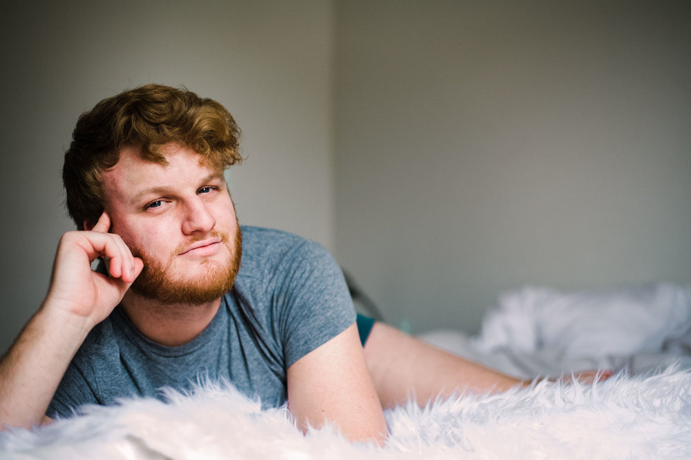 attractive redhead male in a well lit room on a fur bed