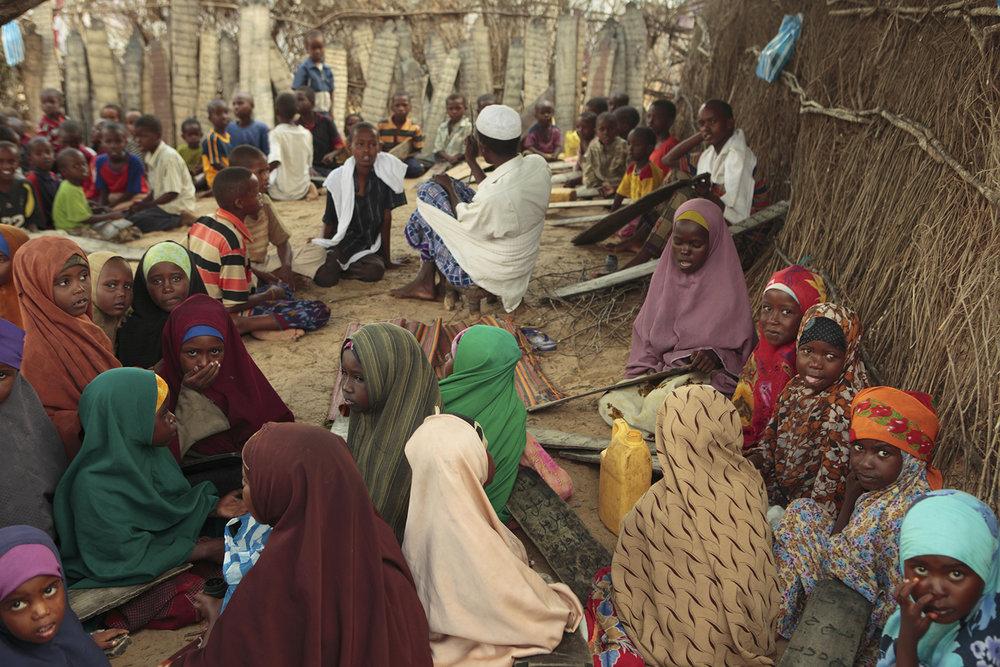 Le professeur récite le Coran avec ses élèves dans une école coranique