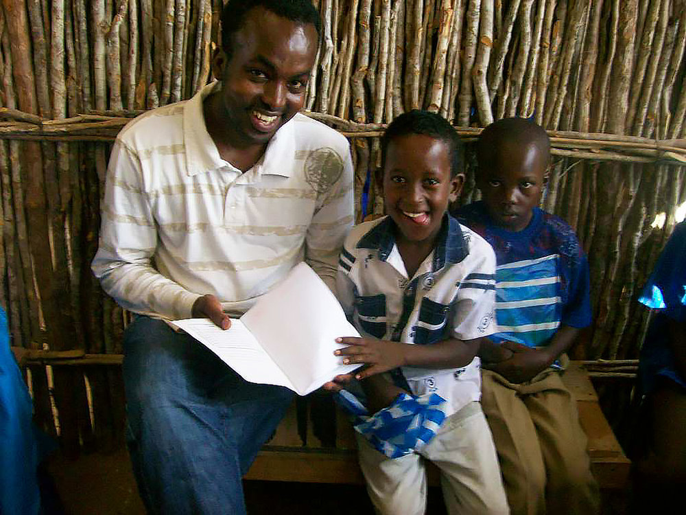 Abdi goes through books with two young students