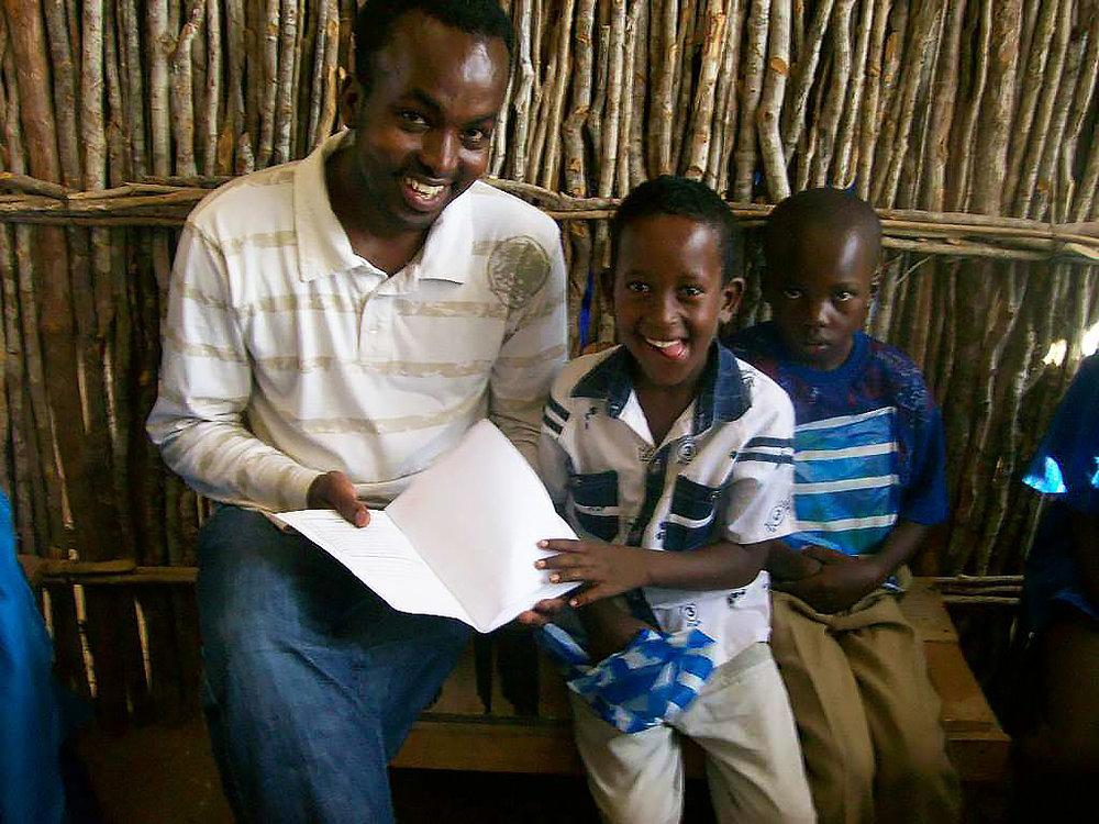 Abdi regarde les livres avec 2 jeunes écoliers