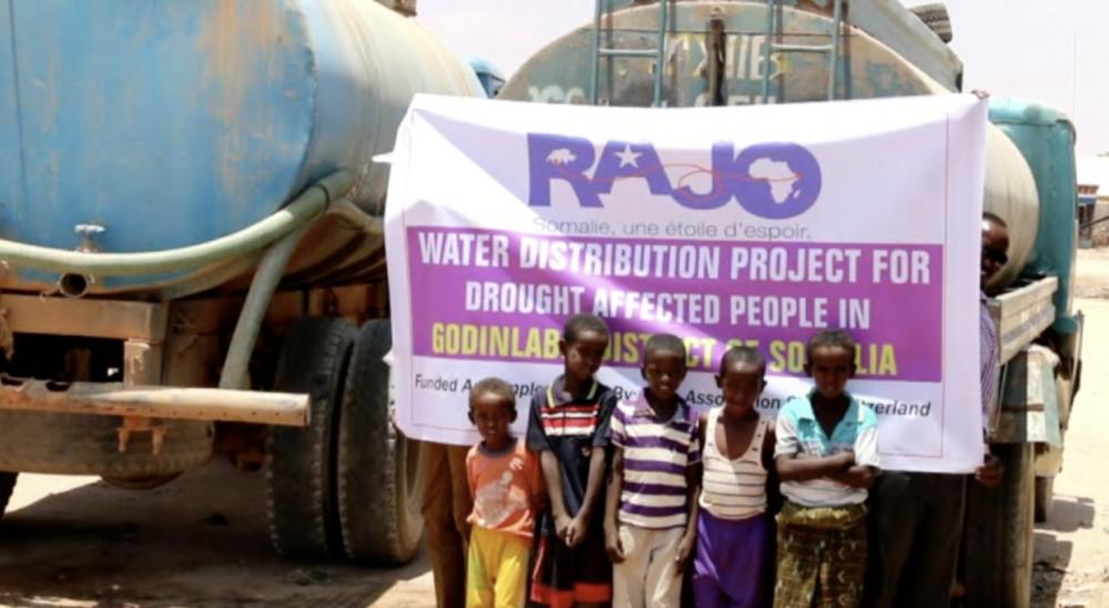 Enfants devant un camion citerne d'eau
