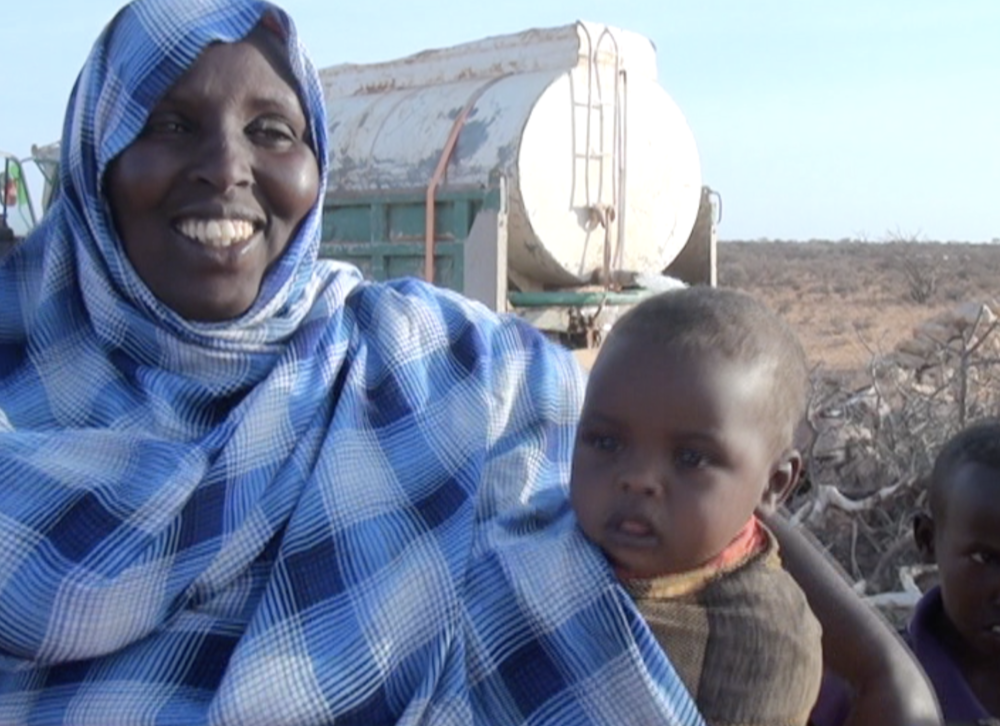 A villager and her baby are happy about the water delivery
