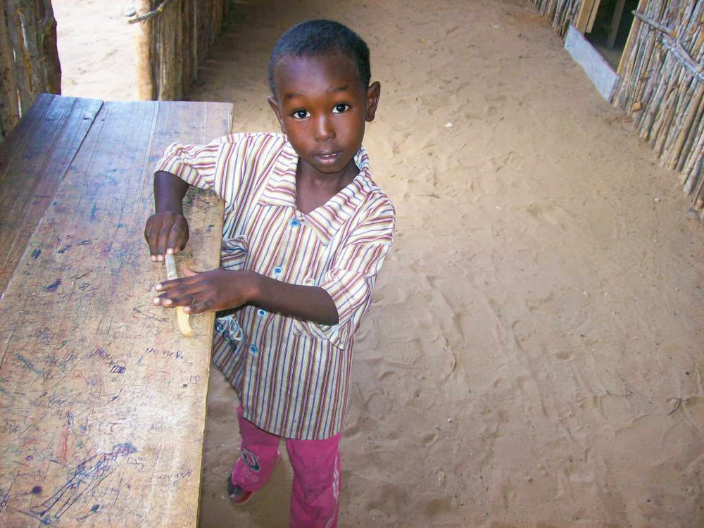 Il attend le retour de ses frères et sœurs qui sont partis à l'école. Camp Hawa Abdi, 2010