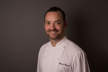 Damien Cassart est tout à la fois notre chef et un des associés de l'entreprise. Son parcours fascinant l'a mené des restaurants gastronomiques les plus prisés de la planète aux gaufres sans gluten de chez Yummy & Guiltfree. Comment ? Pourquoi ? C'est autant de questions que nous éclairons ici !   Damien Cassart, un Belge aux côtés des monuments français dans le monde   Damien Cassart a 15 ans lorsqu'il décide de s'engager dans la gastronomie. Une fois diplômé de boulangerie-pâtisserie en Belgique, il fait ses débuts au Sheraton de Bruxelles et se retrouve rapidement propulsé dans les cuisines les plus prestigieuses du monde : celles du Louis XV d'Alain Ducasse à Monaco (3 étoiles au Guide Michelin), puis celles de Daniel Boulud à New York (2 étoiles)...  C'est à 25 ans qu'il décroche sa première place de chef pâtissier, de retour au Louis XV. Puis, en 2010, son chemin croise celui de Yannick Alléno qui lui propose d'être le chef pâtissier exécutif du Royal Mansour à Marrakech. Trois ans plus tard, il est promu chef pâtissier exécutif du Groupe Yannick Alléno monde et se retrouve donc à la tête de la partie pâtisserie d'un empire gastronomique.   Des palaces à la street food   Damien Cassart entre en contact en 2013 avec Iris et Manoël Collon, co-fondateurs de Yummy & Guiltfree, lorsque Yannick Alléno lui demande de travailler sur leur projet de gaufre sans gluten ni lactose. Après plusieurs mois de collaboration durant lesquels il est le premier à développer une version de la mythique pâte à gaufres, il continue son parcours au sein du groupe Alléno alors qu'Iris et Manoël font appel à d'autres grands noms de la gastronomie pour développer la gamme de gaufres.  Après un an et demi de travail sur Yummy & Guiltfree avec d'autres talents comme Philippe Conticini vient l'heure de pérenniser la marque. Iris et Manoël doivent trouver la perle rare qui permettra à la marque de grandir et d'acquérir une signature gustative cohérente. Ce sera donc Damien Cassart qui reprend