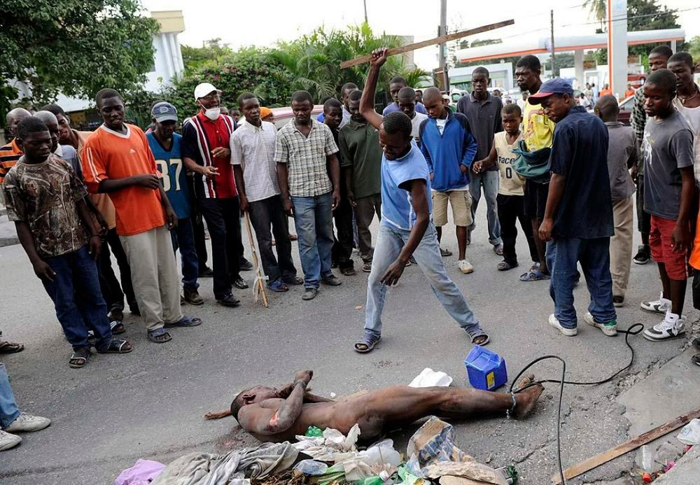 """A photo of a mob delivering Haitian style """"justice"""" to a thief. (photo: BBC)"""