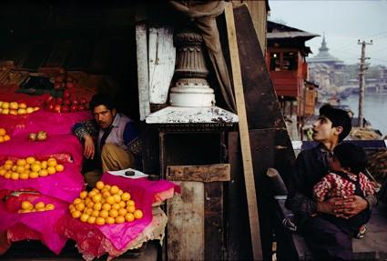 Fruit Seller and a boy with a child at Zaina Kadal Bridge, Jhelum River, Srinagar, Kashmir, 1979.   Raghubir Singh/© 2017 Succession Raghubir Singh
