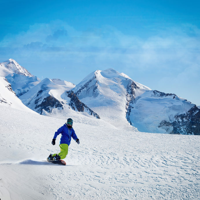70529380 - male snowboarder on the slope with mountain peaks on background