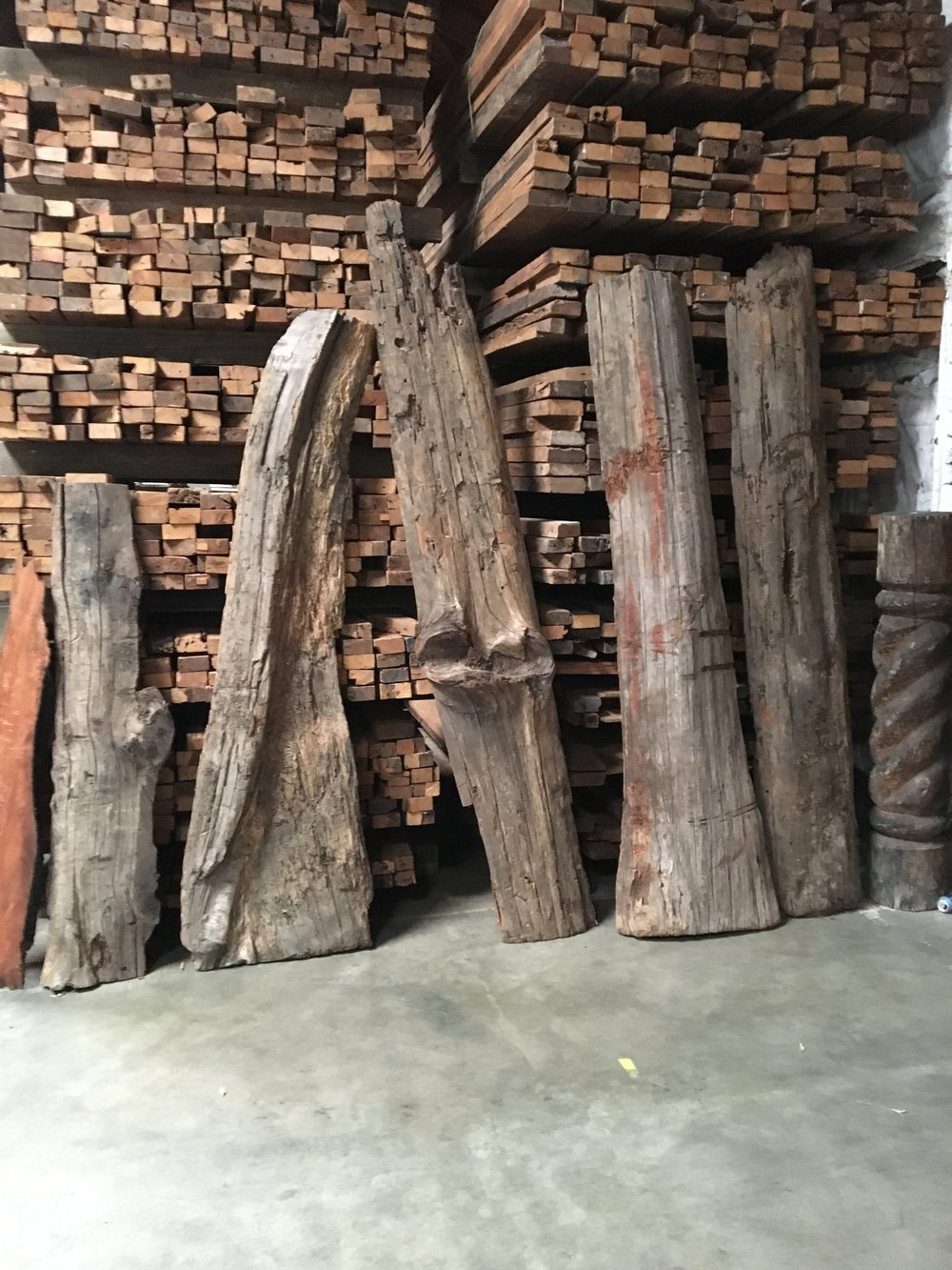 old growth redwood half rounds with stacks of reclaimed hardwood timbers