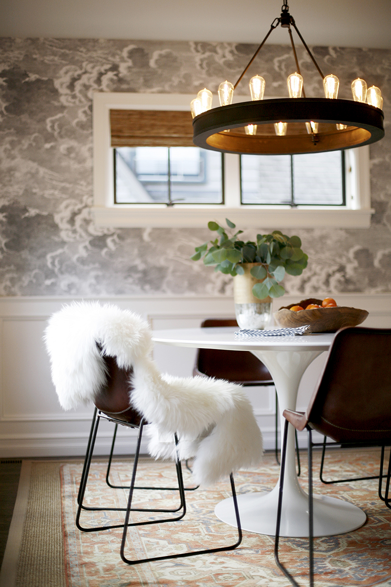 PLAYING UP NEW AND OLD - Modern elements, like the striking Saarinen table and bold wall covering, pair perfectly with the warm leather side chairs and traditional wainscoting.