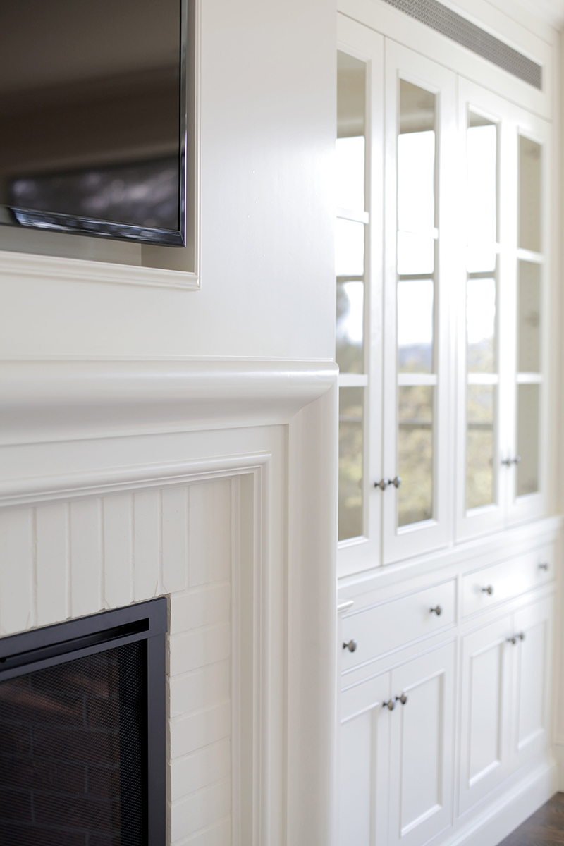 CUSTOMIZED DETAILS - Katie creates a custom wall of cabinetry, equipped with hidden speakers and electronics, surrounding the mantle to achieve a seamless and tidy family room space.