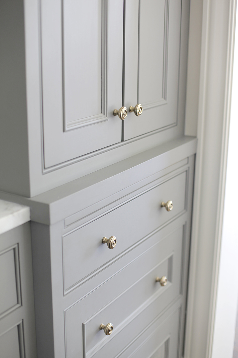 A SENSE OF HISTORY - The inset cabinetry is designed with bolection molds, beaded face frames, and brass hardware. A brush painted finish is applied to give the kitchen a sense of history.