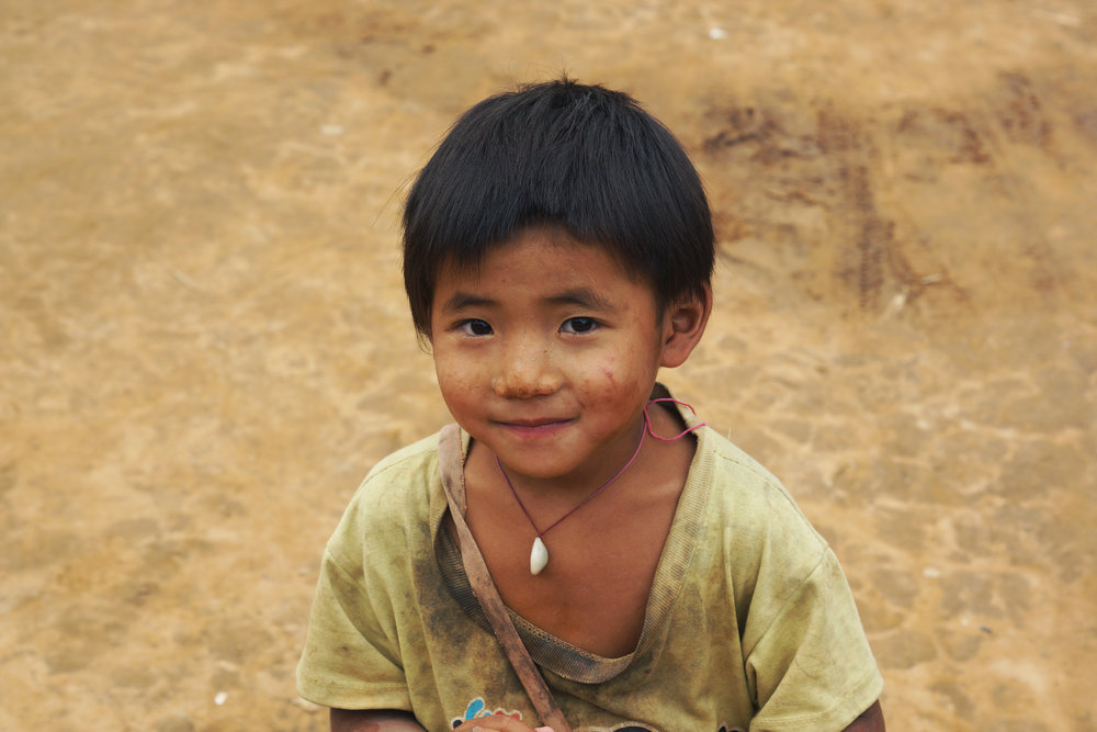 Laos:  In a small village wrecked by poverty, this smiling, happy child was much quieter than his friends.