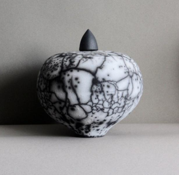 De  Naked Raku  urnen hebben gesprongen glazuur door het gebruik van klei