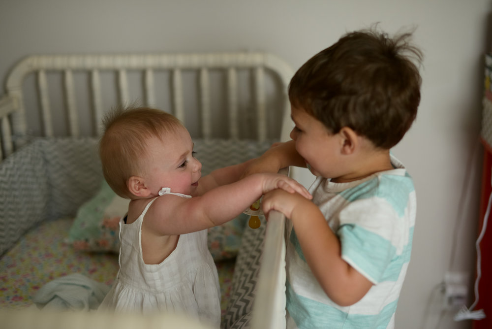 joyful jane photography louisiana lifestyle family photography toddler brother and baby sister holding hands over crib rail