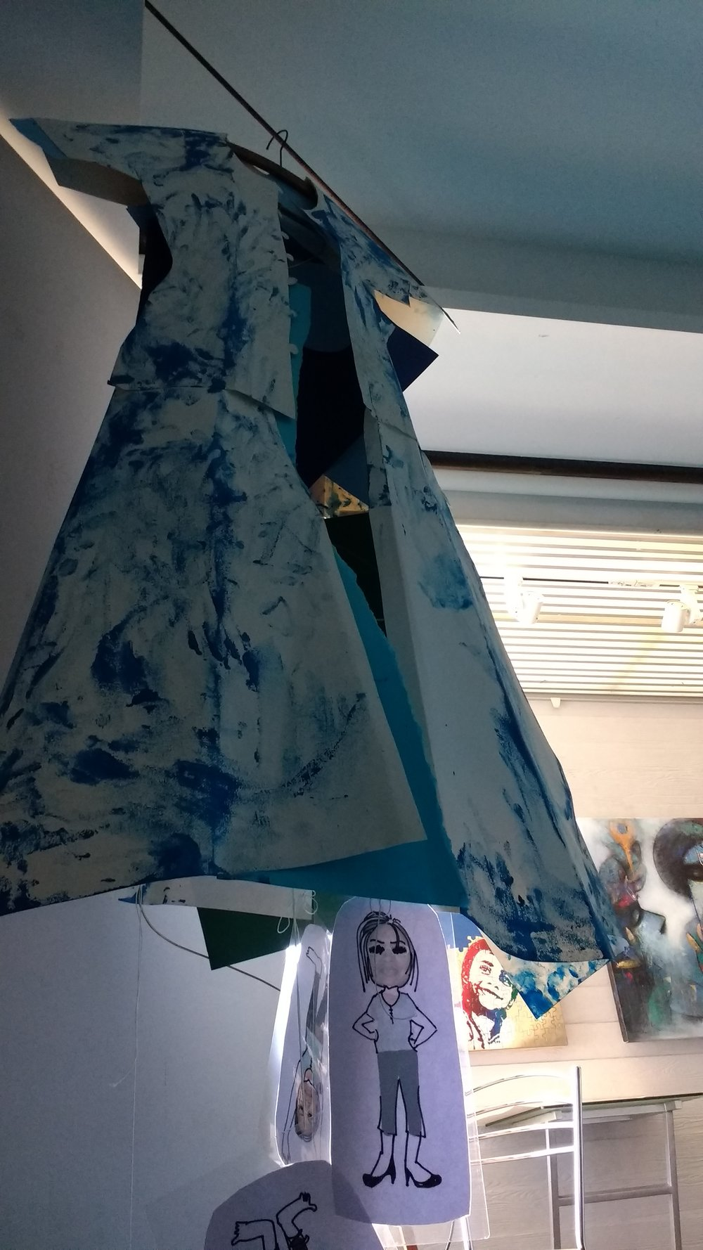 "OUTER BODY, ""THE PAPER DRESS"" I DESIGNED FOR MYSELF, HAD BLUE COLOR STAINS ALL OVER. 'ME' HANGING INSIDE THE EMPTY SPACE,  UPSIDE DOWN, SHAKING BY THE AIR BLOWN THROUGH THE FAN, OPERATING BY THE BATTERY."