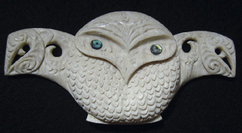 Owl carving with outstretched wings carved as manaia faces