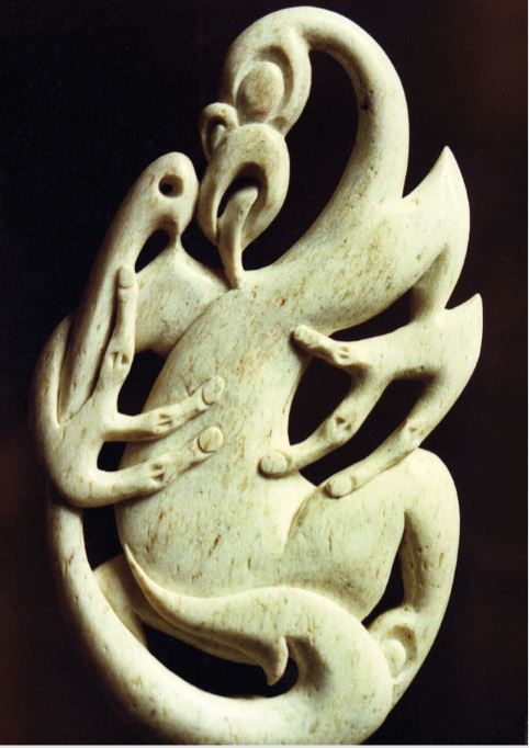 A carving from the jawbone of a sperm whale showing Tangaroa inspecting the artistry of a hei matau. The hook was let down to impress him so that he would reward the fisherman with a good catch of his children, the fish.