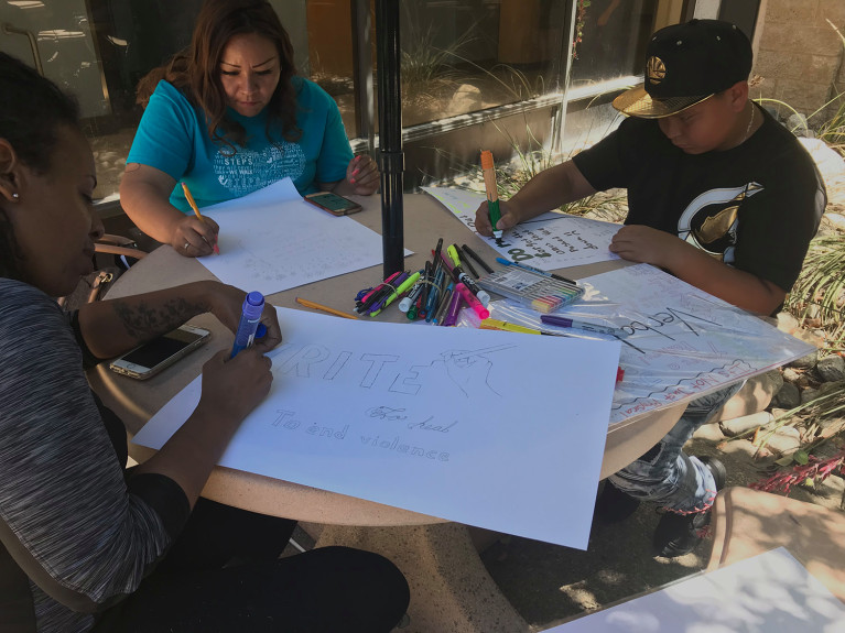As featured in the Press Enterprise, here is Nikia, left, with Karina Cerda, center, and her son Javier Cerda working on their Voices against Violence posters at a recent art and writing workshop. (Photo courtesy Inlandia Institute)