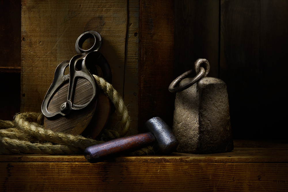 Still life of rope, pulley, and anvil.
