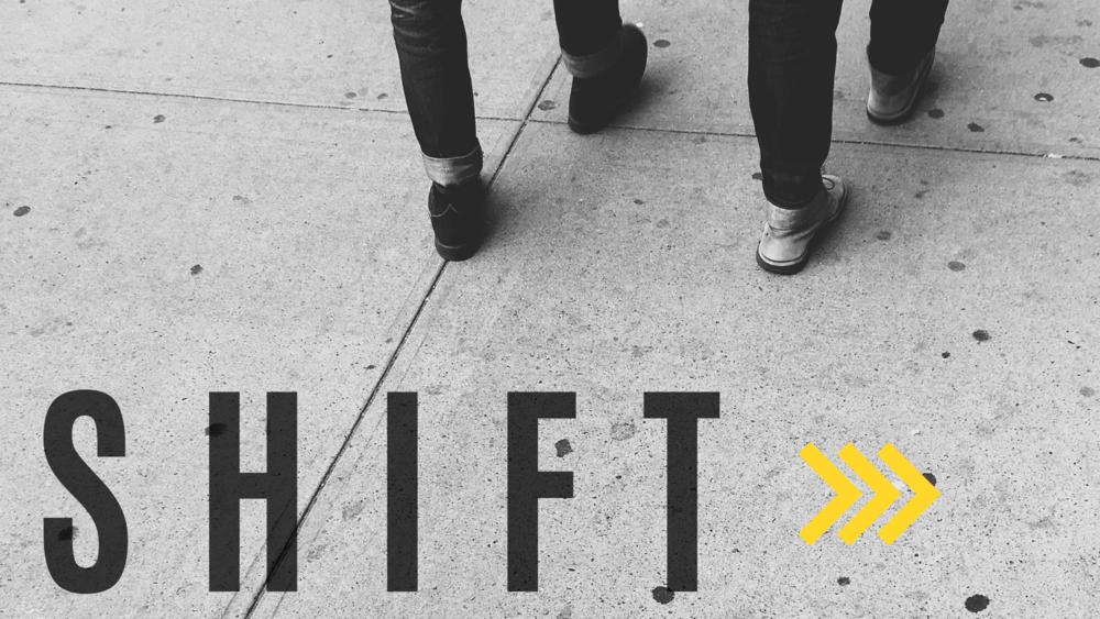 Legs and feet of two people walking along a sidewalk