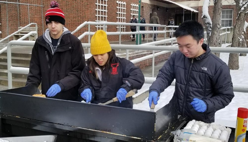 Dom Prudente '19 (left), Charity Kaye (center), and Jason Yang '21 work the grill on an early Friday morning.