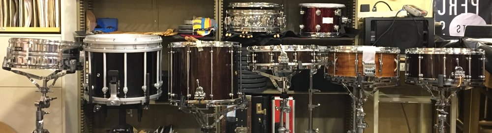 "Snare Drum Alley (L to R): Dixie Steel Snare fitted w. Remo Silent One practice head, Yamaha SfZ 14"" Marching Snare, Pearl Philharmonic 14x12"" Field Drum, Pearl Philharmonic 14x4"" maple Piccolo Snare, Black Swamp Percussion/John Craviatto solid walnut 14x6.5 concert drum, and Pearl Philharmonic 14x6.5"" maple shell."