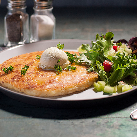 Our highly acclaimed potato pancake with a crust of golden melting cheese, topped with whipped butter and served with a side salad.