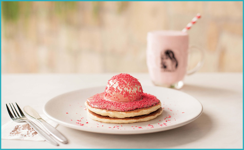Two buttermilk pancakes topped with ice-cream and ruby chocolate fudge, and sprinkled with hundreds and thousands.