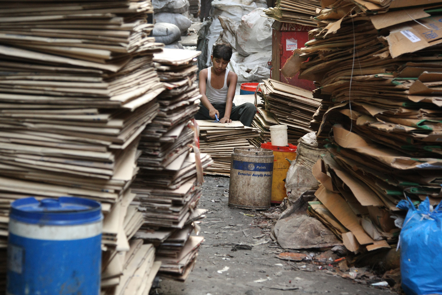 A young boy removes staples from cardboard boxes as part of the recycling process. (Meena Khadri)