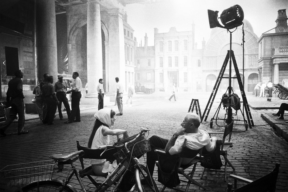 audrey-hepburn-and-george-cukor-on-set-my-fair-lady-covent-garden-london-1963-conde-nast-traveller-14may15-bob-willoughby (1).jpg
