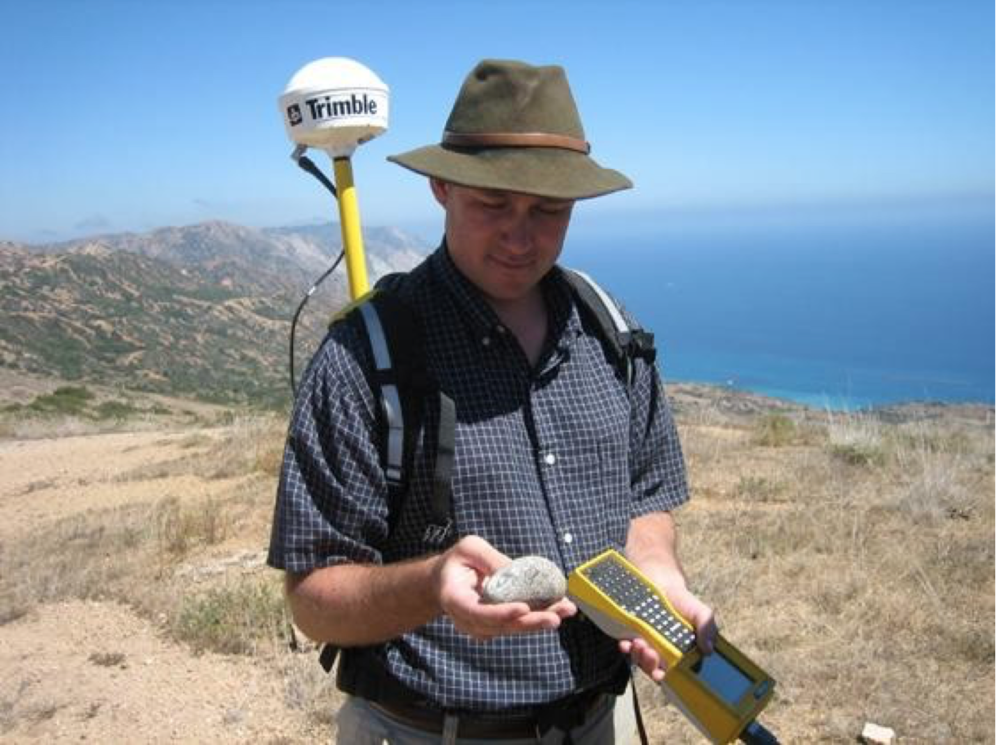 Collin O'Neil, chief of the island survey team, with a ground stone artifact and a sub-meter GPS unit