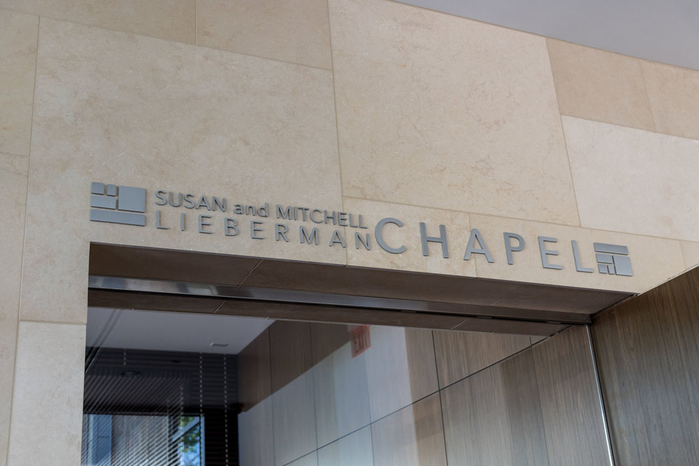 Brushed aluminum dimensional letters  and artwork identifying named area of building.