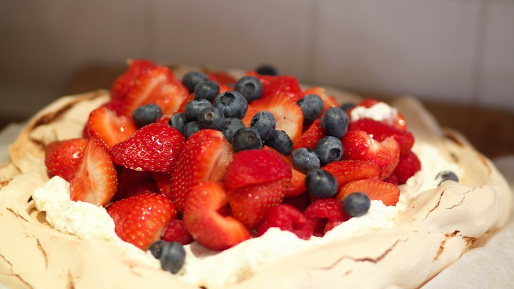 Pavlova topped with fresh berries (a mix of strawberries, raspberries and blueberries) and whipped cream.