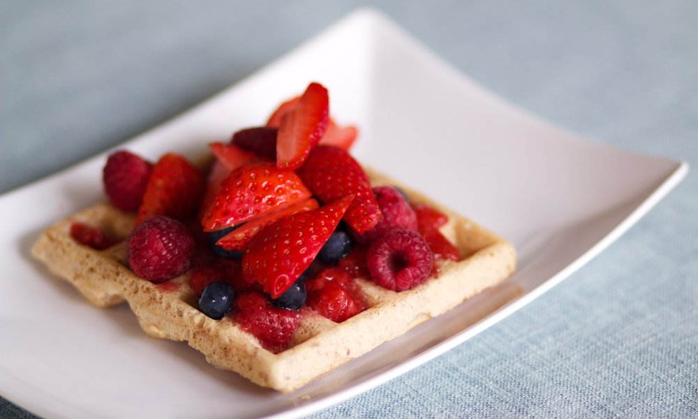 vegan cornmeal waffles topped with strawberry sauce and fresh berries