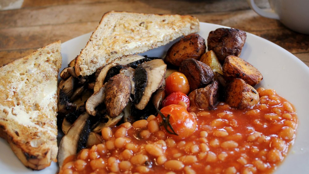 vegan cooked breakfast made up of baked beans, mushrooms, tomatoes, potatoes and bread