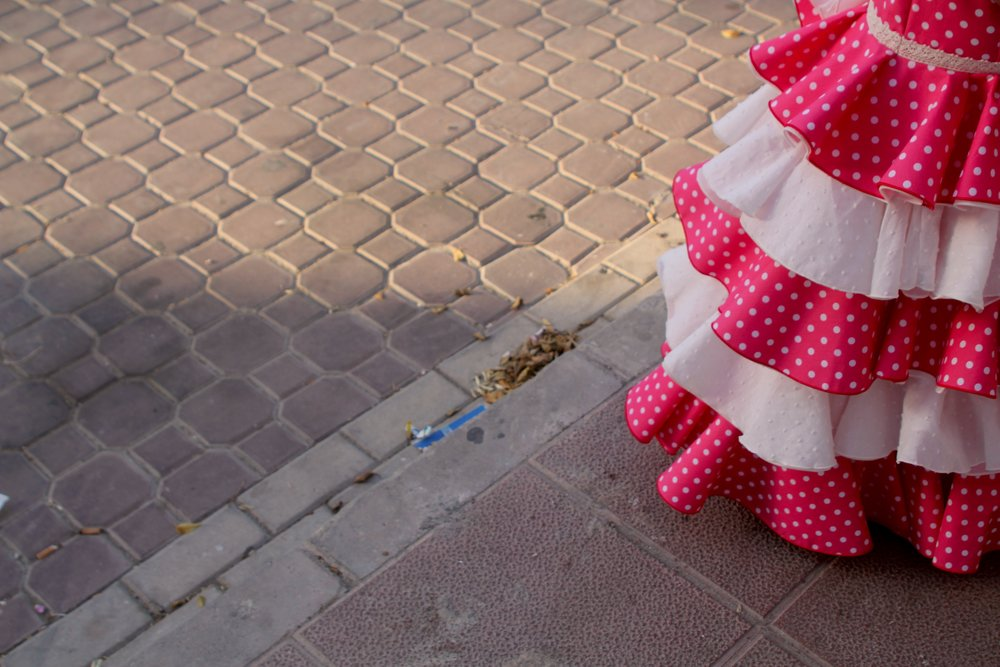 the skirt of a little girl's pink and white feria dress